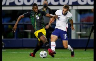 Jamaica forward Cory Burke (9) and United States defender James Sands (16) compete for control of the ball in the first half of  their Gold Cup quarter-final match on Sunday in Arlington, Texas. The United States won 1-0.