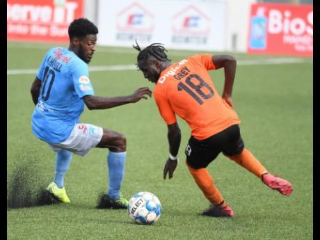 Tivoli's Devroy Grey (right) turns away fom Waterhouse's Denardo Thomas during yesterday's Jamaica Premier League match at the UWI/Captain Horace Burrell Centre of Excellence.