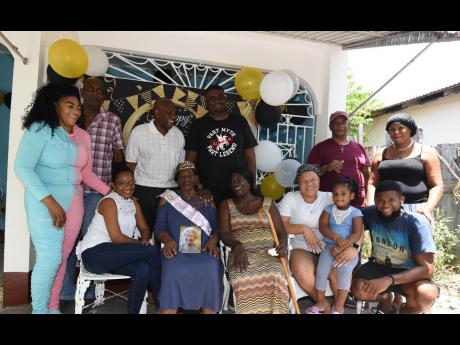 Mercella Pearson (seated, second left) is surrounded by loved ones at her birthday party.