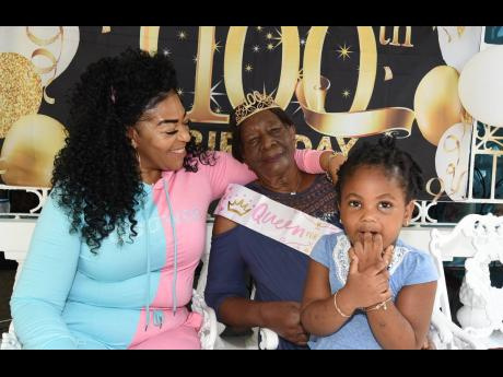 Charmaine Campbell (left) smiles as she looks at Mercella  Pearson during her 100th birthday celebration last Saturday, while Pearson's great-granddaughter, Alaynah Anthony, looks on.