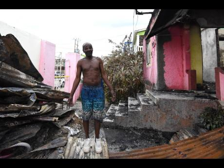 Oscar Palmer stands in the rubble of what used to be his house at East Avenue in Kingston.