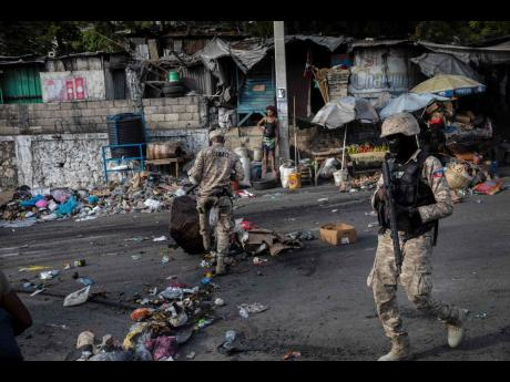 Policemen clean an avenue on Monday that was blocked by protesters and friends and relatives of Biana Velizaire, 27, who was kidnapped for five days by gang members, in Port-au-Prince, Haiti. The police launched a special operation in the most exposed areas of kidnappings to respond to the recent surge in this criminal activity conducted by gangs.