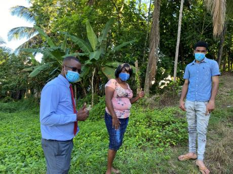 Michael Reid (right) standing beside his mentor, Allan Green (left) and landlord, Gloria Kerr at his home in St James.